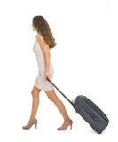 走带着轮子手提箱的少妇 免版税库存图片