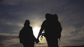 走幸福家庭的游人拿着手剪影在日落 徒步旅行者配合旅行概念 生活方式人和 股票视频