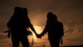 走幸福家庭的游人拿着手剪影在日落 徒步旅行者配合旅行概念 男人和妇女夫妇 股票视频