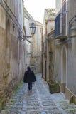 走开在古老,典型的狭窄和鹅卵石街道的未认出的妇女在埃里切,西西里岛,意大利 免版税库存照片