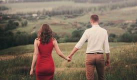 走开在领域,握手的夫妇看法的后面看法夫妇  免版税库存图片