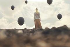 走往无限的孤独的妇女在一个超现实的地方 免版税库存图片