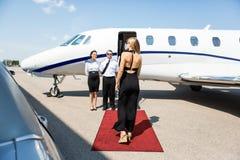 走往私人喷气式飞机的富有的妇女 库存图片