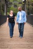 走微笑的人种间的夫妇握手 免版税库存图片