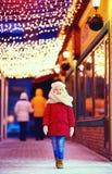 走微笑的年轻的男孩晚上街道,照亮由圣诞灯 库存图片