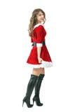 走性感的圣诞老人的女孩侧视图转动顶头和微笑对照相机 库存图片