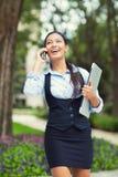 走愉快的繁忙的女商人,当谈话在一个巧妙的电话时 免版税库存照片