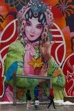 走或等待在巨型壁画前面的人们一辆公共汽车 库存图片