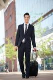 走户外与袋子的英俊的商人 免版税图库摄影
