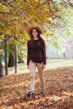 走户外在舒适外套和帽子的秋天公园的幸福微笑年轻女人画象  温暖的晴朗的天气 秋天 免版税库存照片