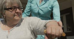 走护士或看守者的帮助的资深夫人协助在红色照相机射击的户外好日子 股票录像