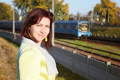 走旅客的妇女和等待在铁路平台的火车 图库摄影