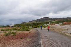 走未认出的游人看Strokkur Geysir在冰岛 免版税库存图片
