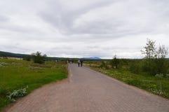 走未认出的游人看Strokkur Geysir在冰岛 免版税库存照片