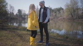 走本质上在城市之外的年轻逗人喜爱的夫妇在河附近 一个黄色雨衣和裂缝的美丽的白肤金发的女孩 股票视频