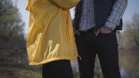走本质上在城市之外的画象年轻逗人喜爱的夫妇在河附近户外 美丽的白肤金发的女孩以黄色 影视素材