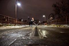 走横跨一座河桥梁的年轻夫妇在城市在晚上在冬天 库存图片