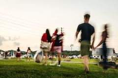 走横跨公园的人的被弄脏的行动到一个室外音乐会 库存图片