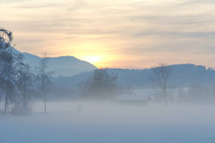 走横跨斯诺伊有薄雾的领域的夫妇 库存图片