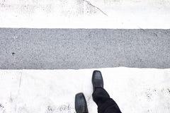 走横跨行人穿越道的商人 黑皮鞋和黑松驰 顶视图 库存照片