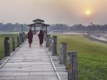 走横跨U Bein桥梁的缅甸修士在日落 免版税图库摄影