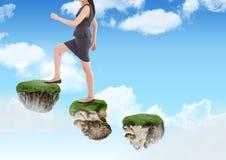 走步的女实业家在天空的浮动岩石平台 免版税库存照片