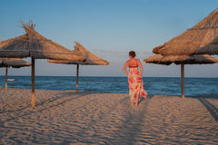 走沿一个沙滩的少妇 免版税库存图片