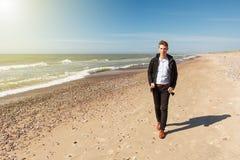 走沿一个空的海滩的一个人 免版税库存照片