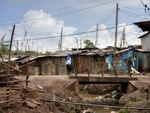 走沿一条开放下水道的人们在一个贫民窟在非洲 库存图片