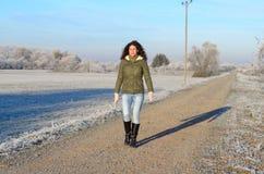 走沿一条结霜的农村路的俏丽的妇女 库存图片