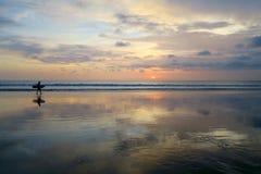 走沿与日落天空的空的库塔海滩的孤独的冲浪者 库存图片