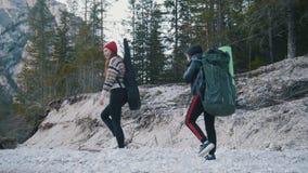 走沿与背包和吉他的岩石河沿的两年轻女人在森林的背景和 股票录像