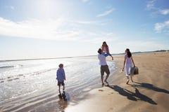 走沿与野餐篮子的海滩的家庭背面图 免版税库存照片