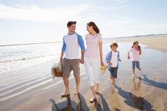 走沿与野餐篮子的海滩的家庭 免版税图库摄影