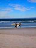 走沿与水橇板的海滩的冲浪者 免版税库存图片
