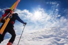 走沿与s的一个陡峭的多雪的土坎的滑雪登山家 免版税库存图片