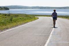 走沿中间路线的孤独的女孩在海和农村风景的背景 图库摄影