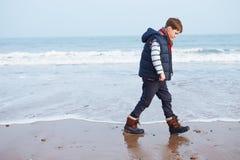 走沿冬天海滩的年轻男孩 免版税库存图片