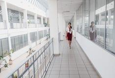 走沿办公室走廊的女商人 微笑的女实业家去反对白色办公室背景 一个新俏丽的女孩 库存照片