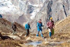 走沿在山谷的冻小河的小组远足者 免版税库存照片
