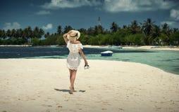 走沿在帽子的海滩的女孩 马尔代夫 沙子白色 海岛 免版税图库摄影