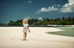 走沿在帽子的海滩的女孩 马尔代夫 沙子白色 海岛 免版税库存图片