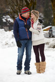 走沿在滑雪胜地的斯诺伊街道的夫妇 免版税库存照片
