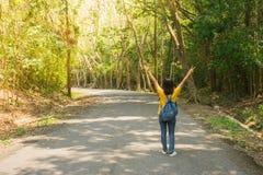 走沿在绿色树中的contryside路的单独妇女旅行家或背包徒步旅行者,她有感觉幸福 图库摄影