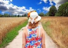 走沿在领域的路的女孩 图库摄影
