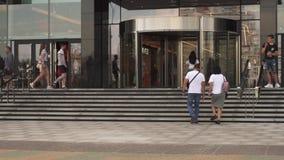 走沿城市街道的人们,在夏日出入商城 股票视频