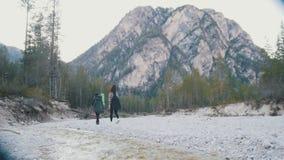 走沿岩石河岸的两年轻女人有背包和吉他的在森林的背景和 影视素材