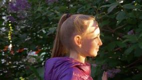 走沿开花的淡紫色树的微笑的女孩在春天城市在好日子 享受春日的愉快的少年女孩  影视素材