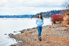 走沿早期的春天或秋天的岩石湖的青少年女孩 免版税库存图片