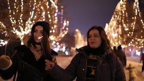 走沿有拿着闪烁发光物的诗歌选的美妙的夜胡同的妇女朋友 影视素材